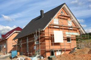 Modernes Einfamilienhaus im Rohbau mit Baugerüst, blauer Himmel und Sonnenschein
